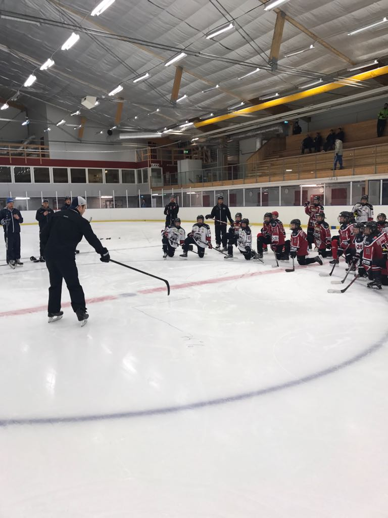Eetu Qvist teaching young ice hockey players proper skating technique.